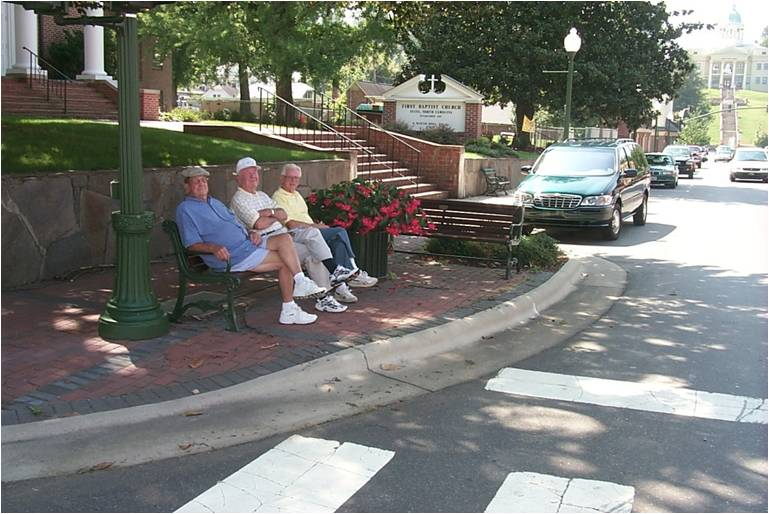 three elderly men sitting on a bench