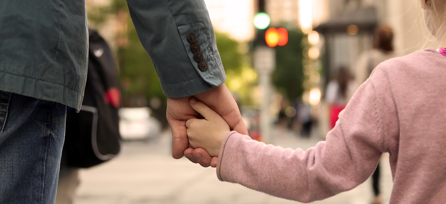 Father holding his daughter's hand at a crosswalk